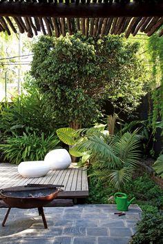 Jardín seco con distintas situaciones de uso. En el centro, solárium con deck y sillones y mesa 'Pastilla' en fibra de vidrio.