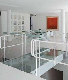No segundo piso, o ambiente unido pela passarela de vidro sobre o vão da escada tem de um lado o home theater e do outro a sala de jantar. Projeto de Hugo Schwartz e Alexandre Gedeon, da InTown.