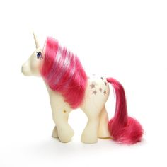 This vintage G1 My Little Pony is Moondancer, she's a unicorn pony from Year 2. She's white with a red tail and has a red mane with a purple streak in it. Her symbol is a glittery silver crescent moon