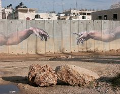 A distant Creation of Adam mural on Israel's illegal apartheid wall.