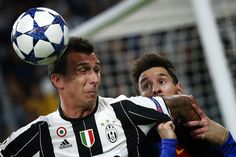Barcelona's forward Lionel Messi from Argentina (R) fights for the ball with Juventus' forward Mario Mandzukic from Croatia during the UEFA Champions League quarter final first leg football match Juventus vs Barcelona, on April 11, 2017 at the Juventus stadium in Turin. / AFP PHOTO / Marco BERTORELLO