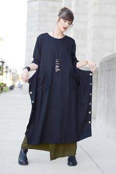 "Square Dress in Black Roma: Longsleeve dress with squared off avant-garde shaped skirt. Has front pockets, and shell buttons along sideseams which can be unbuttoned for a different look -- a great dress to pair with leggings or a skirt! Approx. 51"" (Size S/M) and 56"" (Size M/L) in length."