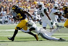 News Photo : Karan Higdon of the Michigan Wolverines tries to...