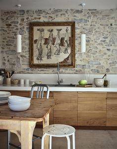 cocina, muebles de madera, encimera blanca y pared de piedra