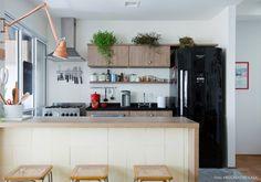 Cozinha aberta com balcão de madeira, geladeira preta e plantinhas em cima do armário.