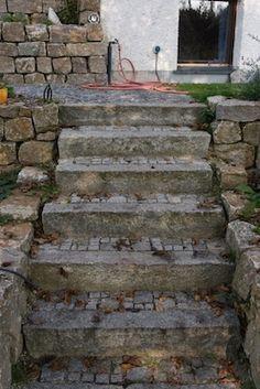 Treppe mit gebrauchten Granit Randsteinen. Auftritte ausgepflastert mit gebrauchtem Granit Kleinstein und Mosaik. Mauereinfassung aus Muschelkalk.