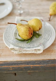 A tablescape with the best of all worlds - rustic, shabby chic, and elegant - starts with a well-worn table and is layered with white dinnerware, a floral cloth napkin, and glass top plate.
