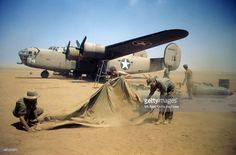 A view as the 376th Bombardment Group work in the blowing sand with a B-24-Liberator in the background at the U.S Air Force Base in Benghazi, Libya.
