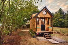 On accède à l'entrée de la tiny house Avonleavia un large porche abrité,muni de deux coffres-bancs d'extérieur et...