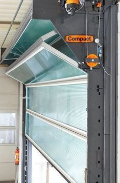 The Compact Industrial Door, Rolflex - this way you have more ceiling storage space in your garage. It also solves the problem of a wet garage door dripping on everything inside when open. Garage House, Garage Shop, Garage Walls, Glass Garage Door, Garage Door With Windows, Garage Bathroom, Garage Cabinets, Dream Garage, Glass Doors