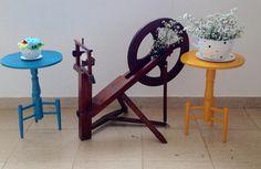Roda de fiar da família, com banquinhos coloridos fazendo um contraste e vasos divertidos com aster.