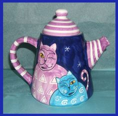 Ceramic tea pot featuring a pair of winking cats in shades of lavender and blue, set against a dark blue starry sky.