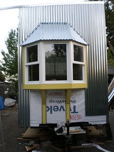 (Jenine Alexander's 2nd tiny house). IDEA: Bay windows/ish out of the bathroom for more space, with the utility garage below -- but only the utility garage supported by the trailer tongue. I have one casement window I can use in the center -- windows or just closed with mirrors on the interior for the other two sides would work.