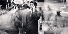 Stock Photo : Asian businessman on cell phone on busy city sidewalk