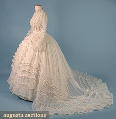 "ORGANDY WEDDING DRESS, c. 1860 April 2006 Vintage Clothing & Textile Auction New Hope, PA 2-piece, trained skirt & bodice w/ bell sleeves, each piece w/ 4 self fabric ruffles decorated w/ cream silk cord, bodice ruched w/ vertical bands of cream silk cord, B 34"", W 24"", Skirt Front L 38"", Back L 70"". Augusta Auctions"