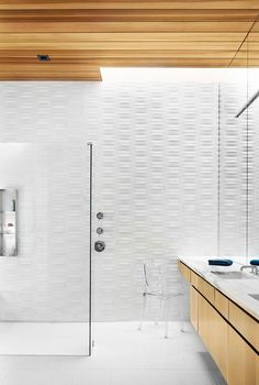 In this modern bathroom, textured white tiles cover the wall, while the wood cabinetry complements the wood ceiling. White Bathroom Tiles, Wood Bathroom, Bathroom Layout, White Tiles, Modern Bathroom Design, Bathroom Small, Modern Bathrooms, Bathroom Ideas, Bathroom Designs