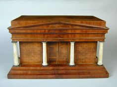 Rare early 19th Century Neo Classical model of a Greek Temple. Executed in mahogany and karelian birch with ebonising and painted decoration. The top lifts to reveal multi compartments with secret drawers. Circa 1825. Probably from Berlin