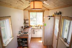 The best cabinetry space use I've seen in a tiny house. Nice ceiling, lighting and beautiful butcher block counter top.