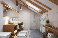carrelage mural blanc neige, poutres apparentes au plafond, meuble de rangement en bois massif et carrelage sol gris