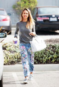 Jessica Alba is casual in a gray sweater, paint-splattered boyfriend jeans, silver sneakers, and a white Kenzo bag