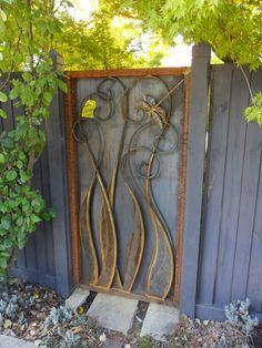 Metal dragonfly frame on wooden garden gate