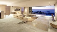 A Large luxury lounge in a modern beach front house tiled with Porcel-Thin large format 1200 x 600mm Sandstone effect ultra-thin porcelain tiles