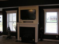 Fireplace surround with TV niche, mantel trim on surrounding windows