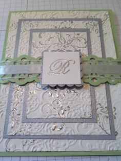 I started with a certainly celery card base and used very vanilla card stock and silver card stock.I embossed the layered very vanilla card stock with the wedding suite stamp set, in silver embossing powder. Before taking the layers apart I ran the layers through the big shot and the lacy brocade embossing folder. Take the layers apart and adhere them to the silver card. Belly band - certainly celery ribbon border punch added 5/8ths organza ribbon,monogram R mounted on scallop square silver
