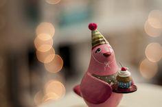 A passarinha rosa está pronta para a festa! Com seu chapeuzinho de aniversário, segura um pratinho com cupcake, seu doce preferido! <br> <br>Exclusivo objeto decorativo feito de papel machê. <br> <br>Dimensões do produto: <br>8 cm de comprimento <br>14,5 cm de altura <br>5 cm de largura