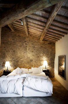 Dormitorio con pared de piedra y techo alto con vigas de madera vista