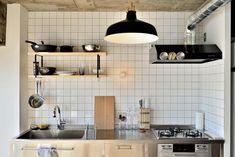 コンパクトなキッチン 白いタイル + 黒い照明