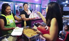 Pinky Cubacub, left, prepares a plate of food for a customer as Jewelyn Vazquez, center, presents another customer with her order at the Liberation Day Carnival on July 13.