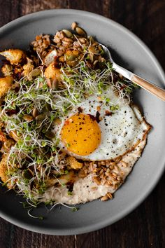 Filling Grain bowls with farro, hummus, smoky roasted cauliflower, fried eggs, and microgreens to complete the dish.