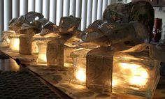 Table Centerpieces - Glass Blocks with battery white lights, tied with ribbon to look like a lit gift box... genius!