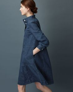 Swingy dress in a soft, washed, indigo-dyed denim. Stand collar, with pleats into back of neck. Four button opening and inverted box pleat below. Long sleeves with double button cuff. Two stitched-through pockets.  Please note - this model is particularly tall, the dress would typically fall below the knee.