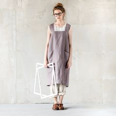 Washed and soft square cross linen pinafore apron is made from 100 % natural European linen. An apron has two big side pockets which are divided into two more (totally 4 pockets).  +++++++++++++++++++++++++++++++++++++++++++++++++++++++++++++ WHAT MAKES YOUR ITEM SPECIAL  Our items are handmade in small studio in small quantities of washed linen fabric, specially woven for us by our local linen manufacturers. The procedure of making these items takes time and effort, cause the items are…