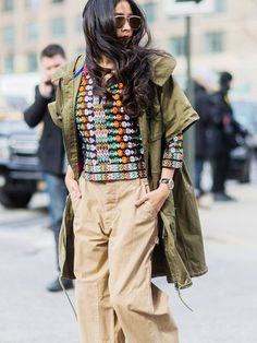 A green utility jacket is worn with a patterned crop top and wide leg khaki pants