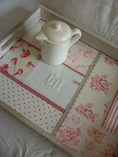 I'm guessing you glue fabric pieces down on a wood tray and cover the seams with trim.  Nice idea for drawer dividers too!