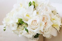 Vendela roses, white Majolica spray roses, cymbidiums, freesia and hydrangea. An ivory ribbon with rhinestone trim completes the look