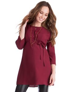 Adjustable buttoned neckline   Concealed zip nursing access  Detachable self-tie empire belt   ¾ sleeves   Mid-thigh length    Made in premium woven crepe viscose in a stunning burgundy shade, this maternity tunic is a versatile style, perfect for dressing up or down. The easy loose fit drapes beautifully over your figure, finishing mid-thigh to cover your curves, while a detachable self-tie belt secures at the empire waist to define your shape. Sleek covered buttons at the neckline can be…