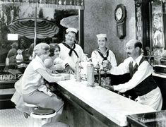 """Laurel and Hardy, James Finlayson, Anne Cornwall and Gloria Greer ordering sodas in """"Men O' War."""""""