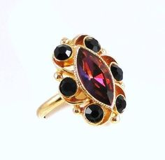 Vintage Adventure eBay listing ends March 11, 2014. Vintage Sarah Coventry JAVA ring features a marquise rhinestone that flashes purple, pink and smoky amber colors, reminiscent of heliotrope, surrounded by black rhinestone chatons. This elegant cocktail style ring is set in glossy goldtone metal with a brushed goldtone backing. Band, which is signed Sarah Cov. on interior, is adjustable. Featured in 1974 Sarah Coventry Summer Catalog.