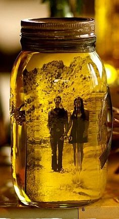 I love how she made her own wedding centerpieces by placing black and white photos into vegetable oil-filled mason jars. The oil preserves the photograph and gives it an aged yellowing effect. She added a sprig of dried lavender to make it smell nice.  @Katie Dorothy another thing to try with your mason jars