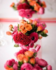 Roses, ranunculus, and Celosia cristata are grouped in low white vessels.