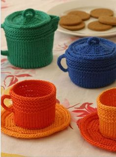 Knitting Pattern for Fiesta Tea Set - A tea party inspired by the simple style of Fiestaware dishes includes cup, saucer, creamer, sugar bowl, pitcher, and plaid placemat. Great as toys, decor, or to hold sugar or tea packets. Except for the placemat, all the pieces begin with the same circular base, so the set is a whole lot easier to knit than you might think. Pieces vary from 2″ (5 cm) high to 3″ (7.5 cm) high