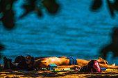 Homem toma sol deitada na praia do Perequê em Ilhabela, Brasil