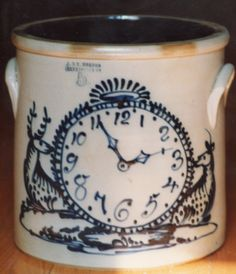 Unique 5 gal. crock with a large clock set for 2:56 with two reclining deer as bookends all on a ground cover. Rare