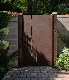 Custom made corten steel entry gate is laser cut to mimic the inlays in the walnut entry door. Phot: Aaron Leitz
