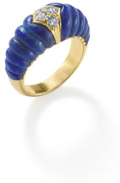 A lapis lazuli and diamond ring, by Cartier  The carved lapis lazuli set to the centre with brilliant-cut diamonds within an 18-carat gold lozenge-shaped plaque, ring size N, signed 'Cartier London', full UK import marks