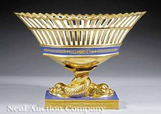 433. A Paris Porcelain Bleu Royale and Gilt-Decorated Corbeille, navette-form reticulated basket, on intertwined dolphin standard, rectangular plinth base, height 12 1/4 in., length 16 1/2 in., width 8 3/4 in. $6000/8000